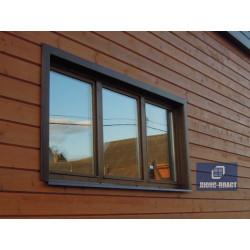 фрагмент деревянного дома с окном с коричневым отливом и коричневыми откосами из металла